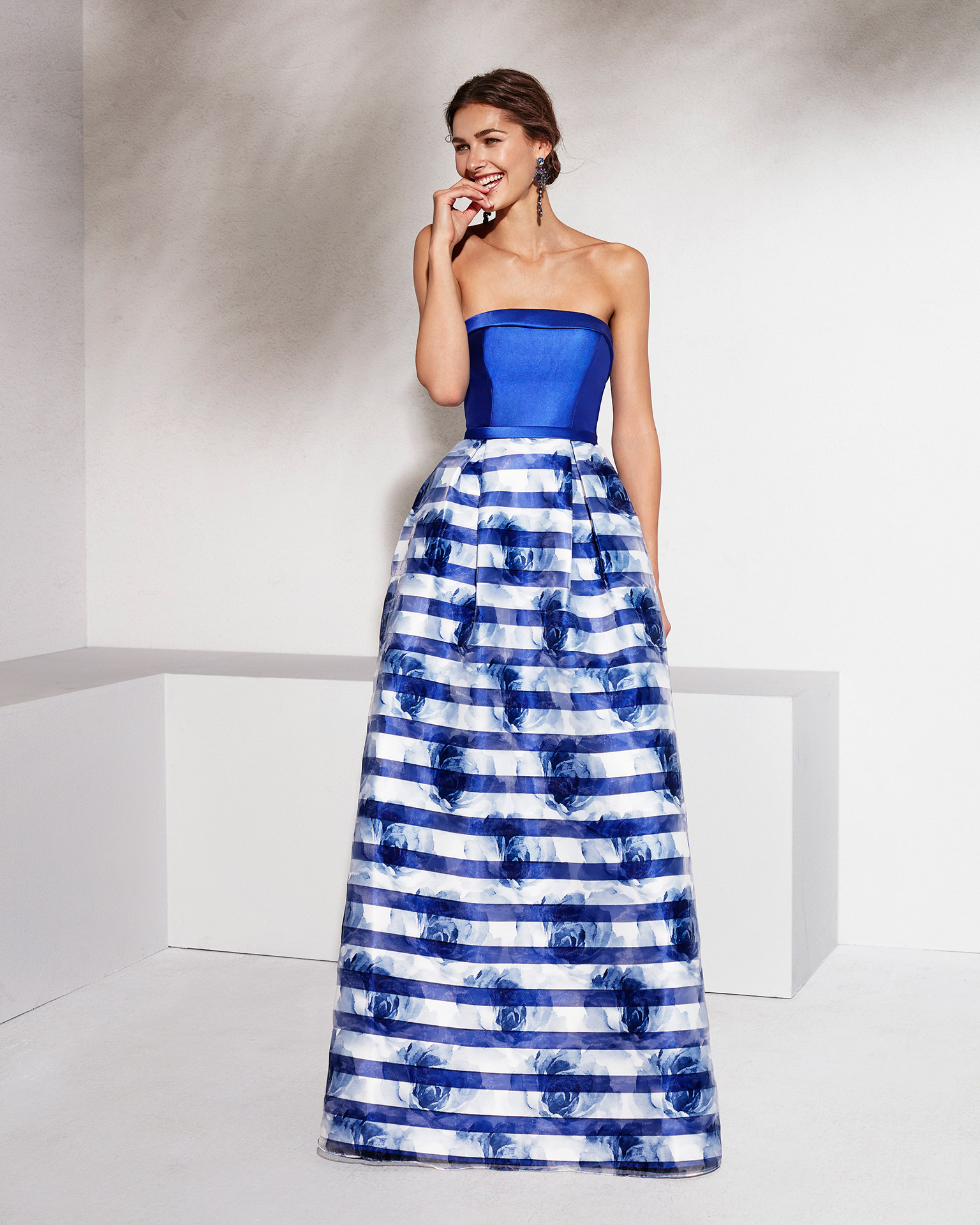Long organza and mikado cocktail dress with strapless neckline. Available in black/coral print, cobalt/cobalt print and silver/silver print. 2018 MARFIL BARCELONA Collection.