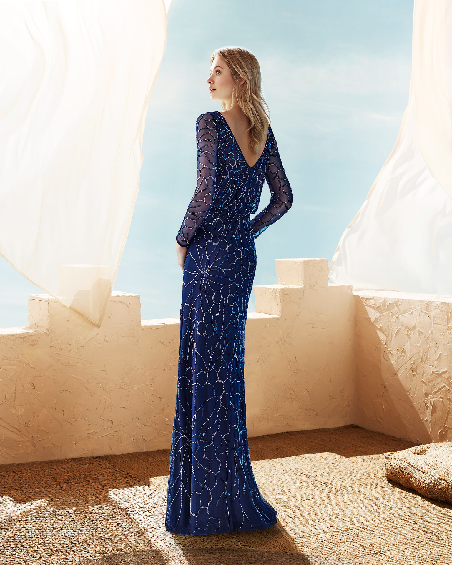 Long beaded bloused cocktail dress with V-back and long sleeves. Available in navy blue, nude/silver and red. 2020 MARFIL BARCELONA Collection.