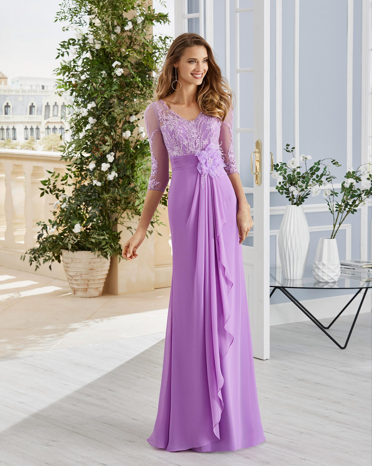 Vestido de fiesta en gasa con encaje y pedrería en el cuerpo. Escote en V, lazo con flor en el frente y drapeado en la falda. Colección COUTURE CLUB 2020.