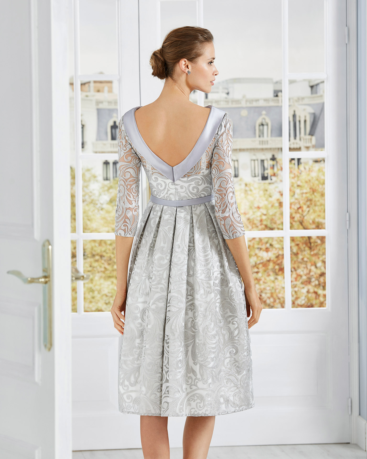 Short lace cocktail dress. Bateau neckline with three-quarter lace sleeves and bow at the waist. 2020 COUTURE CLUB Collection.