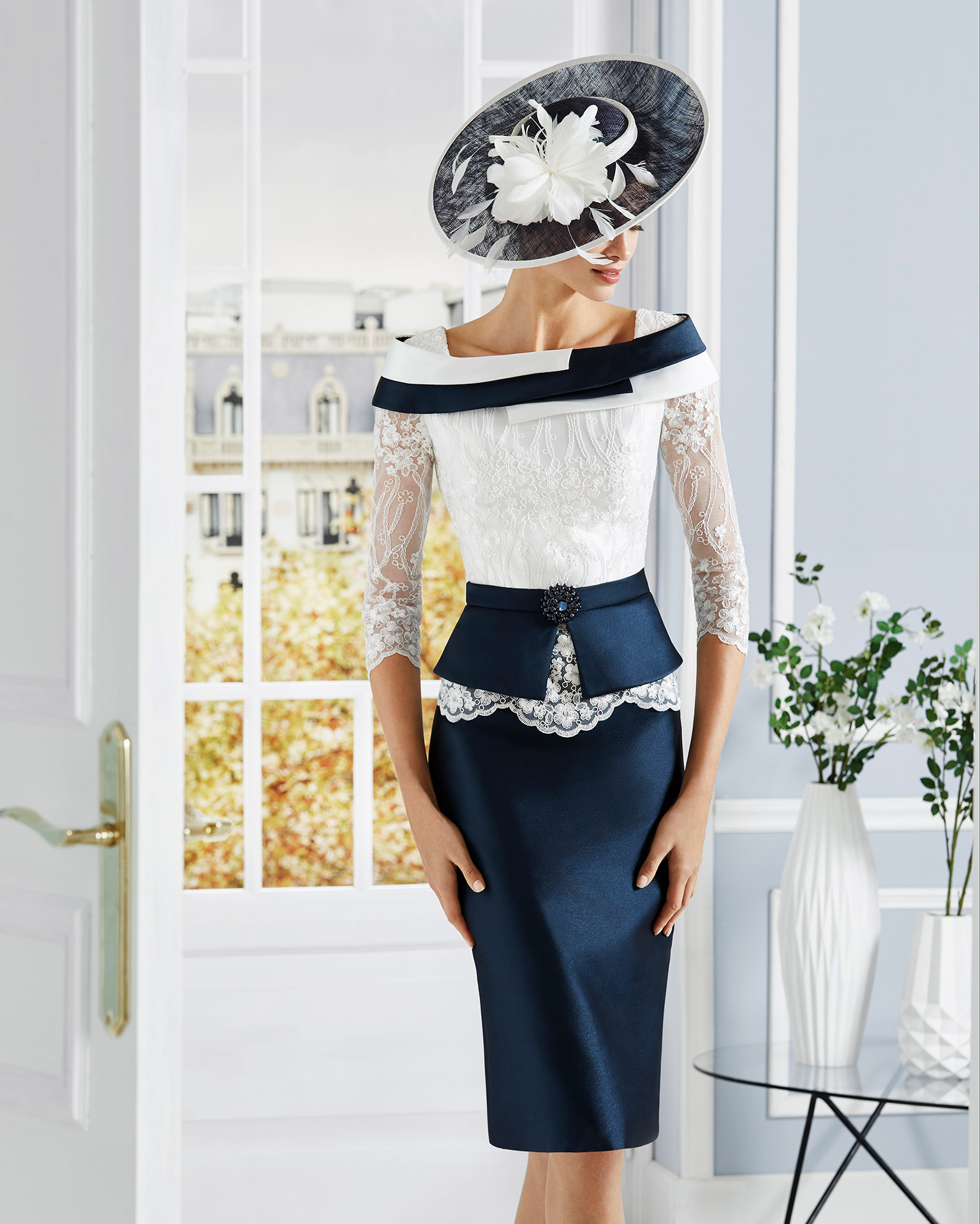 Short cocktail dress in mikado with lace on the bodice and brooche of beading at the waist. Off-the-shoulder neckline and three-quarter lace sleeves. 2020 COUTURE CLUB Collection.