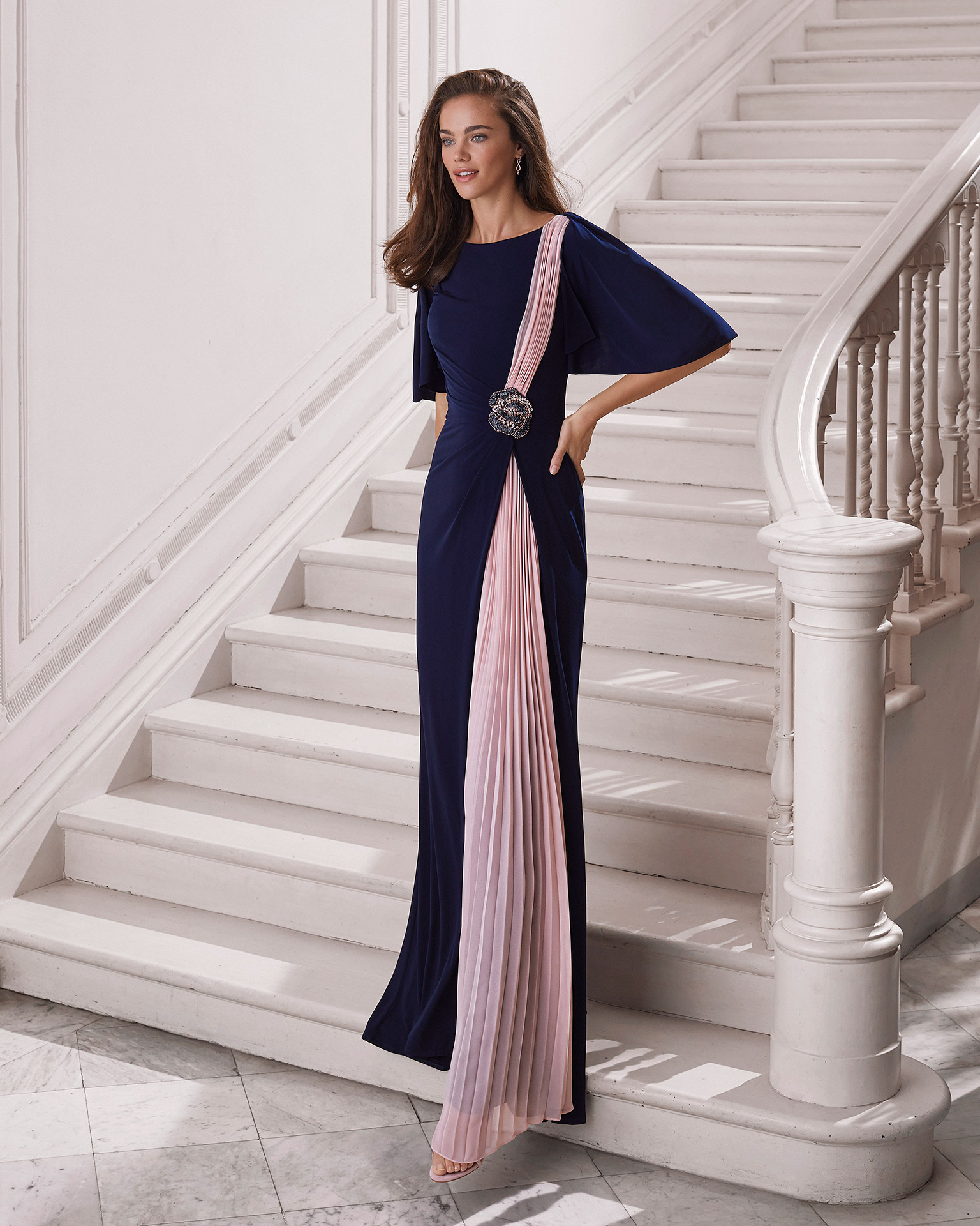 Cocktail dress in knit. Bateau neckline and closed back. With asymmetrical pleated detail at front of dress and beaded clasp on front at side. 2021 MARFIL BARCELONA Collection.