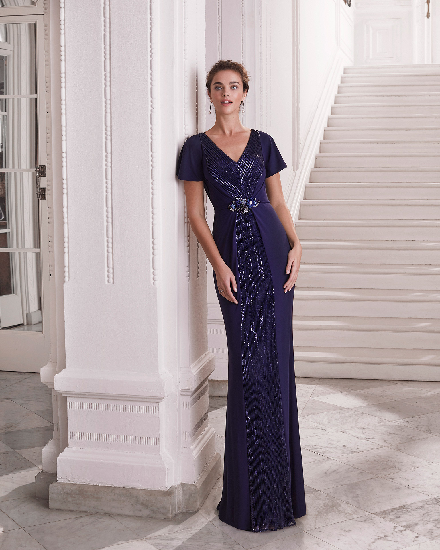 Cocktail dress in embroidered knit with sequins. V-neckline and closed back. Short cape sleeves, and beaded clasp in centre of dress at front. 2021 MARFIL BARCELONA Collection.