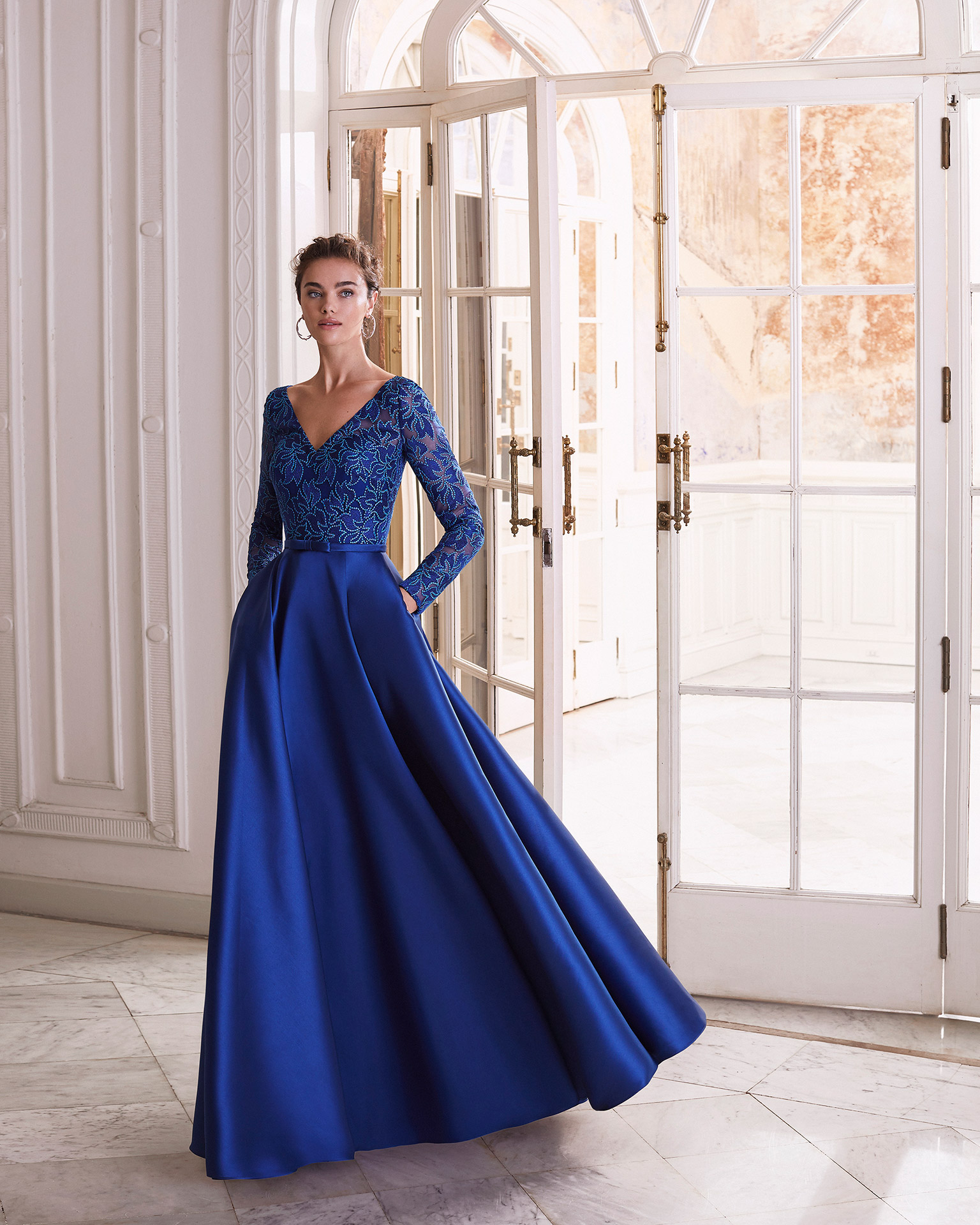 Cocktail dress in mikado with lace bodice. With V-neckline and V-back. Long sleeves and thin belt with bow in centre of dress. 2021 MARFIL BARCELONA Collection.